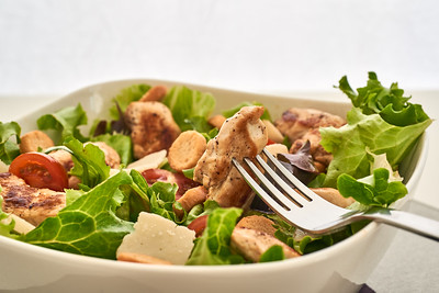 A cesar salad and a chunk of chicken in a fork