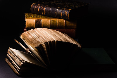 horizontal long shot of an old book with his sheets deployed ahead others old books with a hard-focus and black background