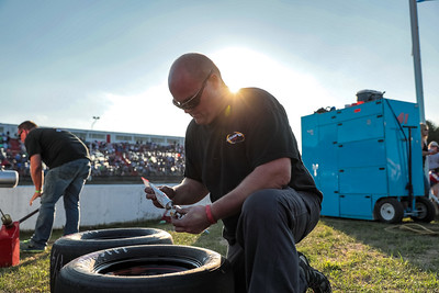 Before the race begins, Ben Gonyea glues lug nuts on the the extra set of tires kept in the pit during the race for driver Kelly Moore of Scarborough.