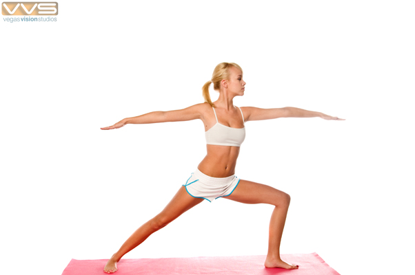 Athletic blond woman stretching on a yoga mat