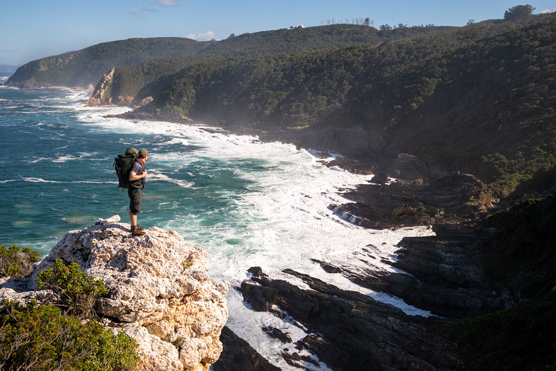 Otter Trail man sea cliff viewpoint with hiking bag, Eastern Cape, South Africa