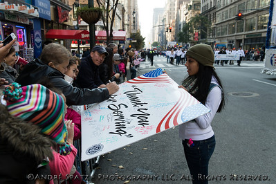 """Spectators signing """"Thank You for Serving"""" signs to be handed out to the Veterans."""