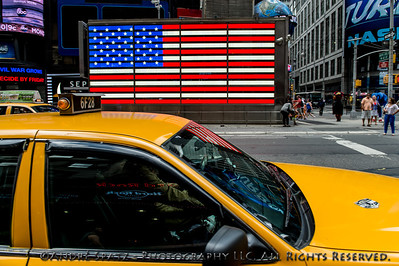 Flag reflections on the NYC taxi from the U.S. Armed Forces Recruitment Center in Times Square.