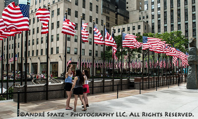 Tourists snapping pictures of the US Flags around the Rockefeller Center on the 4th of July