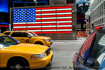 Flag reflections on the NYC taxi and SUV from the U.S. Armed Forces Recruitment Center in Times Square.