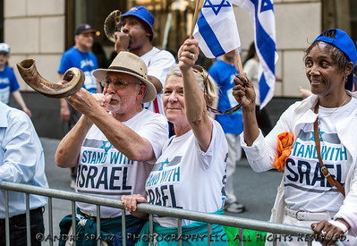Spectators stnading with Israel and blowing the Shofar Horn