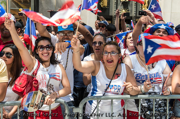 Huge crowds celebrating the Puerto Rican Day Parade on Fifth Avenue with flags.