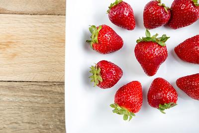 Arrangement of strawberries on white dish.