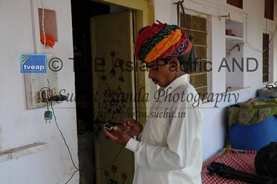 Mobile phone use in Rural Rajasthan (Village near Pushkar): Sayar Singh who stays Chamunda Matha Road, Pushkar, Rajasthan, India recharing his handphone.