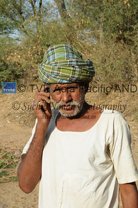 Mobile phone use in Rural Rajasthan (Village near Pushkar): Father of Sayar Singh talking on the mobile phone to keep in contact. Sayar Singh, Chamunda Matha Road, Pushkar, Rajasthan, India.