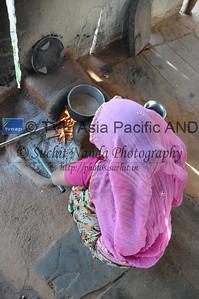 Mobile phone use in Rural Rajasthan (Village near Pushkar): Sister of Sayar Singh doing this house hold work. Sayar Singh, Chamunda Matha Road, Pushkar, Rajasthan, India.