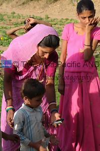 Mobile phone use in Rural Rajasthan (Village near Pushkar): Family members of Sayar Singh using the phone at Chamunda Matha Road, Pushkar, Rajasthan, India.