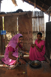 Mobile phone use in Rural Rajasthan (Village near Pushkar): Sister of Sayar Singh doing this house hold work and talking on the mobile phone. Sayar Singh, Chamunda Matha Road, Pushkar, Rajasthan, India.