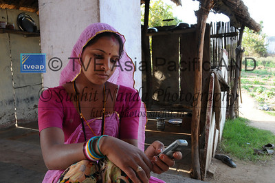 Mobile phone use in Rural Rajasthan (Village near Pushkar): Sister of Sayar Singh using the mobile phone. Sayar Singh, Chamunda Matha Road, Pushkar, Rajasthan, India.