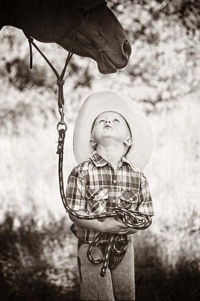 Young boy lookin up at his horse... black and white