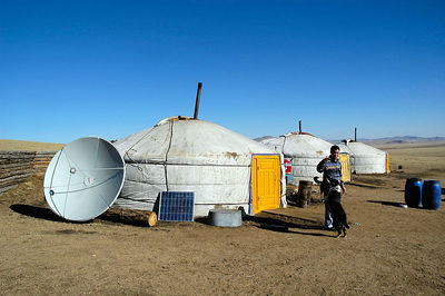Gir with satellite dish and solar panel in Gobi desert, Mongolia.