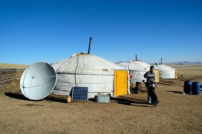Gir with satellite dish and solar panel in Gobi desert, Mongolia.