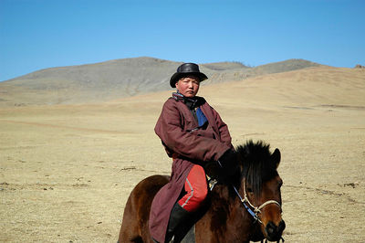 Boy on a horse in Gobi desert, Mongolia