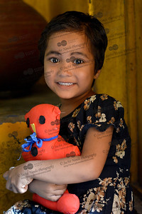 Young girl clutching her toy at the Mobile Creches, Seemapuri Centre.  Mobile Creches works with birth to 12 year old children living on the construction sites and slums of Delhi(NCR) since 1969. Integrated Daycare Centers for children on construction sites are run. Mobile Creches has so far reached out to 7,50,000 children, trained 6,500 women as childcare workers, run 650 daycare centres and partnered with 200 builders.  Mobile Creches runs daycares centres where children are provided education, nutrition and healthcare. Community-women and NGOs are trained to provide care and speak-up for the child. The years of experience along with strong-networks helps in the advocacy for policy-change.