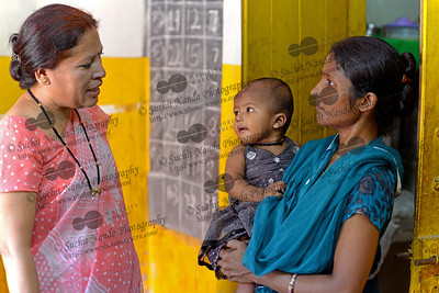 Mother discussing the development of her child at the Mobile Creches, Seemapuri Centre.  Mobile Creches works with birth to 12 year old children living on the construction sites and slums of Delhi(NCR) since 1969. Integrated Daycare Centers for children on construction sites are run. Mobile Creches has so far reached out to 7,50,000 children, trained 6,500 women as childcare workers, run 650 daycare centres and partnered with 200 builders.  Mobile Creches runs daycares centres where children are provided education, nutrition and healthcare. Community-women and NGOs are trained to provide care and speak-up for the child. The years of experience along with strong-networks helps in the advocacy for policy-change.