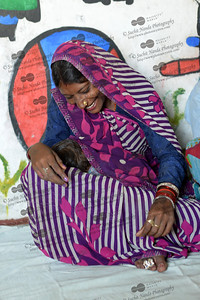 Ram Ratan, a young mother breast-feeds her baby taking time out from the construction work that she is doing by visiting the Mobile Creches, located very close to the construction site at Vatika-83, Gurgaon, Delhi, NCR.  Mobile Creches works with birth to 12 year old children living on the construction sites and slums of Delhi(NCR) since 1969. Integrated Daycare Centers for children on construction sites are run. Mobile Creches has so far reached out to 7,50,000 children, trained 6,500 women as childcare workers, run 650 daycare centres and partnered with 200 builders.  Mobile Creches runs daycares centres where children are provided education, nutrition and healthcare. Community-women and NGOs are trained to provide care and speak-up for the child. The years of experience along with strong-networks helps in the advocacy for policy-change.