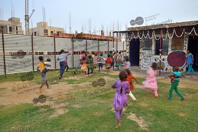 Children rushing to see the Lokdoot Natya Manch, Mobile Creches Theatre Group play at Mobile Creches, Vatika-83, Gurgaon, Delhi, NCR.  Mobile Creches works with birth to 12 year old children living on the construction sites and slums of Delhi(NCR) since 1969. Integrated Daycare Centers for children on construction sites are run. Mobile Creches has so far reached out to 7,50,000 children, trained 6,500 women as childcare workers, run 650 daycare centres and partnered with 200 builders.  Mobile Creches runs daycares centres where children are provided education, nutrition and healthcare. Community-women and NGOs are trained to provide care and speak-up for the child. The years of experience along with strong-networks helps in the advocacy for policy-change.