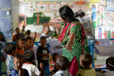 Rinku, a staff of Mobile Creches showing how a bird takes flight at the  Mobile Creches, Vatika-83, Gurgaon, Delhi, NCR.  Mobile Creches works with birth to 12 year old children living on the construction sites and slums of Delhi(NCR) since 1969. Integrated Daycare Centers for children on construction sites are run. Mobile Creches has so far reached out to 7,50,000 children, trained 6,500 women as childcare workers, run 650 daycare centres and partnered with 200 builders.  Mobile Creches runs daycares centres where children are provided education, nutrition and healthcare. Community-women and NGOs are trained to provide care and speak-up for the child. The years of experience along with strong-networks helps in the advocacy for policy-change.