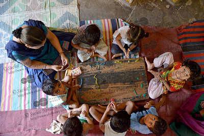 Children through play learning hand-eye co-ordination at the Mobile Creches, Seemapuri Centre.  Mobile Creches works with birth to 12 year old children living on the construction sites and slums of Delhi(NCR) since 1969. Integrated Daycare Centers for children on construction sites are run. Mobile Creches has so far reached out to 7,50,000 children, trained 6,500 women as childcare workers, run 650 daycare centres and partnered with 200 builders.  Mobile Creches runs daycares centres where children are provided education, nutrition and healthcare. Community-women and NGOs are trained to provide care and speak-up for the child. The years of experience along with strong-networks helps in the advocacy for policy-change.