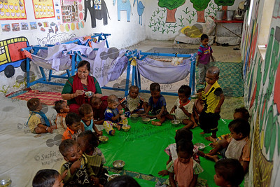 Young children having their afternoon meal at the Mobile Creches, Vatika-83, Gurgaon, Delhi, NCR.  Mobile Creches works with birth to 12 year old children living on the construction sites and slums of Delhi(NCR) since 1969. Integrated Daycare Centers for children on construction sites are run. Mobile Creches has so far reached out to 7,50,000 children, trained 6,500 women as childcare workers, run 650 daycare centres and partnered with 200 builders.  Mobile Creches runs daycares centres where children are provided education, nutrition and healthcare. Community-women and NGOs are trained to provide care and speak-up for the child. The years of experience along with strong-networks helps in the advocacy for policy-change.