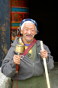 """Old Buddhist man in Bhutan. Seen in the image is a prayer wheel which is rotated. Each rotation is considered a prayer said, so the people walk turning this prayer wheel around.  This image has been used full page in """"The Big Earth Book"""" authored by James Bruges ISBN: 978-1-901970-87-6 which is published by Alastair Sawday Publishing, 2007"""