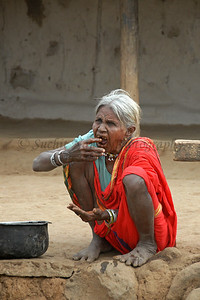 India: This old lady sitting in front of her home is using a paste made from local herbs to clean her teeth. Medical services are rather poor and insufficient in such villages near Nagpur, Maharashtra. Jan 2007.