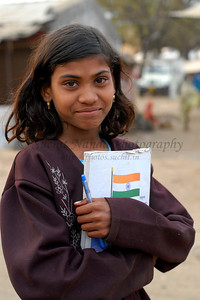 India: This young girl clutching her notebook was headed to her school. Quite noticable is the Indian flag on her book cover. Jan 2007.