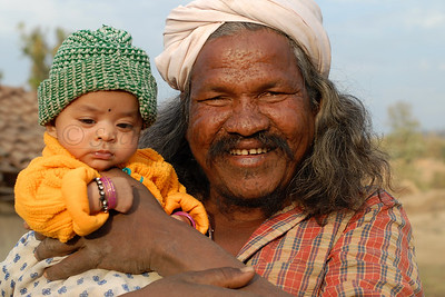 India: Grandfather holding the little girl in a village near Nagpur, Maharashtra. Jan 2007.