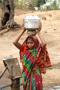 India: This young lady had placed one vessle of water on her head and is preparing for the multiple others that will go on top in which she will carry the water from the local village hand pump in a village near Nagpur, Maharashtra. Jan 2007.