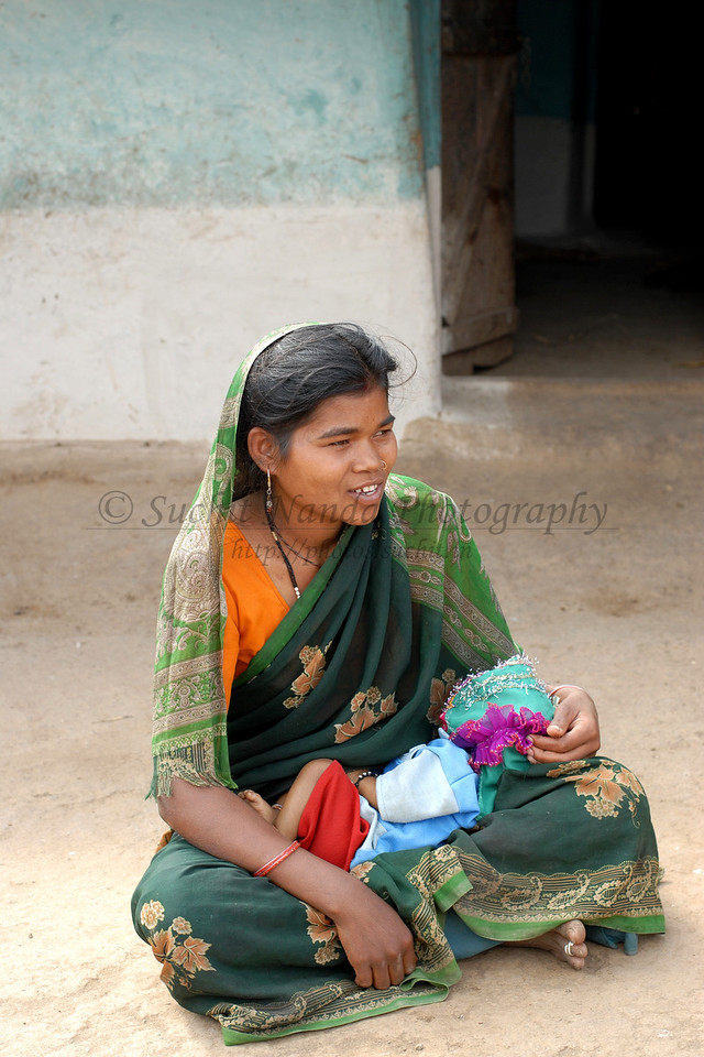 India: A mother sitting at the entrance to her home after breast feeding her child in a village near Nagpur, Maharashtra. Jan 2007.
