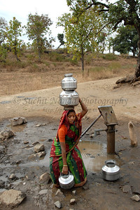 India: This young lady is bending to pick the the pots that she will carry on her head and in her hands from the local village hand pump in a village near Nagpur, Maharashtra. Jan 2007.