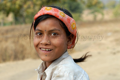 India: Saw this girl with this colourful head scarf filling water at the local village hand pump and got a close up portait of her. Jan 2007.