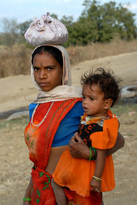 India: Mother and daughter walking with a small pouch carrying typically food to her village near Nagpur, Maharashtra. Jan 2007.