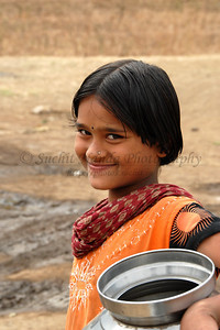 India: Young children typically girls carry vessels filled with water from the local village hand pump to their homes as part of their daily chores in a village near Nagpur, Maharashtra. Jan 2007.