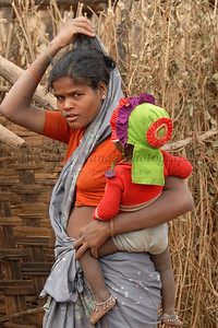 India: Mother with her girl child was walking in her village. It is customary for women to cover their heads when meeting men that are not their family members or elders. This lady walking with her child was caught in the act of covering her head. Jan 2007.