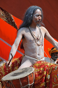 With the beating of drums and on horses and other vehicles arrives the procession of Naga sadhus who as per tradition have the first right of bathing in the holy Ganga on the occasion of Shahi Snan in Kumbh Mela.   Kumbh Mela is the biggest religious gatherings on the planet which takes places on the banks of the river Ganga. The number of pilgrims this year is expected to exceed around five million since the first day Jan 14 till the time it concludes on April 28, 2010. The auspicious days of the shahi snan or royal baths usually draw hundreds of thousands of devotees to the Har Ki Paudi and other banks of the river. Uttarakhand. North India. The occasion draws pilgrims from around the world and severly overloads the infrastructure so most of the city is shut down for any vehicles other than security or emergency services so a sea of humanity walks through the city to get to the bathing ghats.