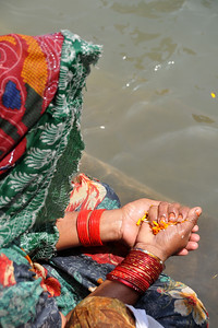 Lady performing a religious ritual at the Kumbh Mela, Haridwar.  Kumbh Mela is the biggest religious gatherings on the planet which takes places on the banks of the river Ganga. The number of pilgrims this year is expected to exceed around five million since the first day Jan 14 till the time it concludes on April 28, 2010. The auspicious days of the shahi snan or royal baths usually draw hundreds of thousands of devotees to the Har Ki Paudi and other banks of the river. Uttarakhand. North India.