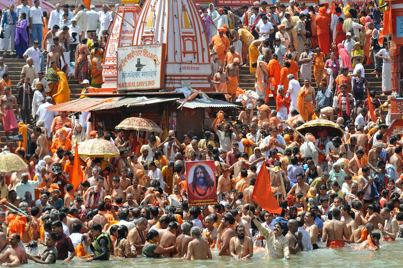 Naga sadhus (naked monks) jump into the river ganga with frenzy. As per tradition, the Naga sadhu's have the first right of bathing in the holy Ganga on the occasion of Kumbh Mela.<br /> <br /> <br /> Kumbh Mela is the biggest religious gatherings on the planet which takes places on the banks of the river Ganga. The number of pilgrims this year is expected to exceed around five million since the first day Jan 14 till the time it concludes on April 28, 2010. The auspicious days of the shahi snan or royal baths usually draw hundreds of thousands of devotees to the Har Ki Paudi and other banks of the river. Uttarakhand. North India. The occasion draws pilgrims from around the world and severly overloads the infrastructure so most of the city is shut down for any vehicles other than security or emergency services so a sea of humanity walks through the city to get to the bathing ghats.