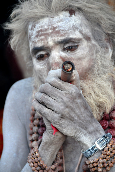 Naga Sadhu with his chillam at Kumbh Mela, Haridwar.<br /> <br /> Kumbh Mela is the biggest religious gatherings on the planet which takes places on the banks of the river Ganga. The number of pilgrims this year is expected to exceed around five million since the first day Jan 14 till the time it concludes on April 28, 2010. The auspicious days of the shahi snan or royal baths usually draw hundreds of thousands of devotees to the Har Ki Paudi and other banks of the river. Uttarakhand. North India.