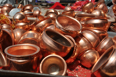 Small copper/brass vessels being sold in the street shops. These vessels are used to lift off small quantities of water to pour as a form of prayer. The vessels are taken back as a form of blessed item.  Kumbh Mela is the biggest religious gatherings on the planet which takes places on the banks of the river Ganga. The number of pilgrims this year is expected to exceed around five million since the first day Jan 14 till the time it concludes on April 28, 2010. The auspicious days of the shahi snan or royal baths usually draw hundreds of thousands of devotees to the Har Ki Paudi and other banks of the river. Uttarakhand. North India. The occasion draws pilgrims from around the world and severly overloads the infrastructure so most of the city is shut down for any vehicles other than security or emergency services so a sea of humanity walks through the city to get to the bathing ghats.