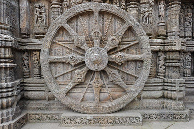 Detailed work done in stone on the massive stone wheels of Konark Sun Temple.  Konark Sun Temple in Orissa belongs to the Kalinga school of Indian temples and was constructed by King Narasimhadeva of the Eastern Ganga Dynasty in the 13th Century. This world heritage site temple takes the form of a colossal chariot of Surya (Sun) drawn by seven spirited horses on twelve pairs of exquitely decorated wheels. Surya has been a popular deity in India since the Vedic perios. Thousands of sculptured images depict deities, celestial and human musicians, dancers, lovers, and myriad scenes of courtly life, ranging from hunts and military battles to the pleasures of courtly relaxation. The temple is famous for its erotic stone sculptures, which can be found primarily on the second level of the porch structure.