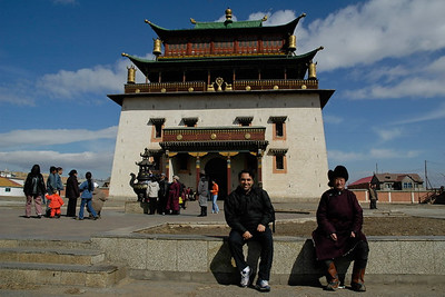 Facade of Janraisig Datsan, Gandan Khiid - Gandantegchinlen Khiid Monastery. Ulan Bator (Ulaanbaatar), Mongolia. Suchit taking a short break just as another Mongolian man.