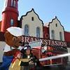 Bamse med brannkonstabel og barn som slukker brann foran brannstasjonen - Høydebilde