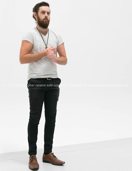 Trendy young man standing against white background.