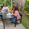 Four women in discussion around table in conservatory area